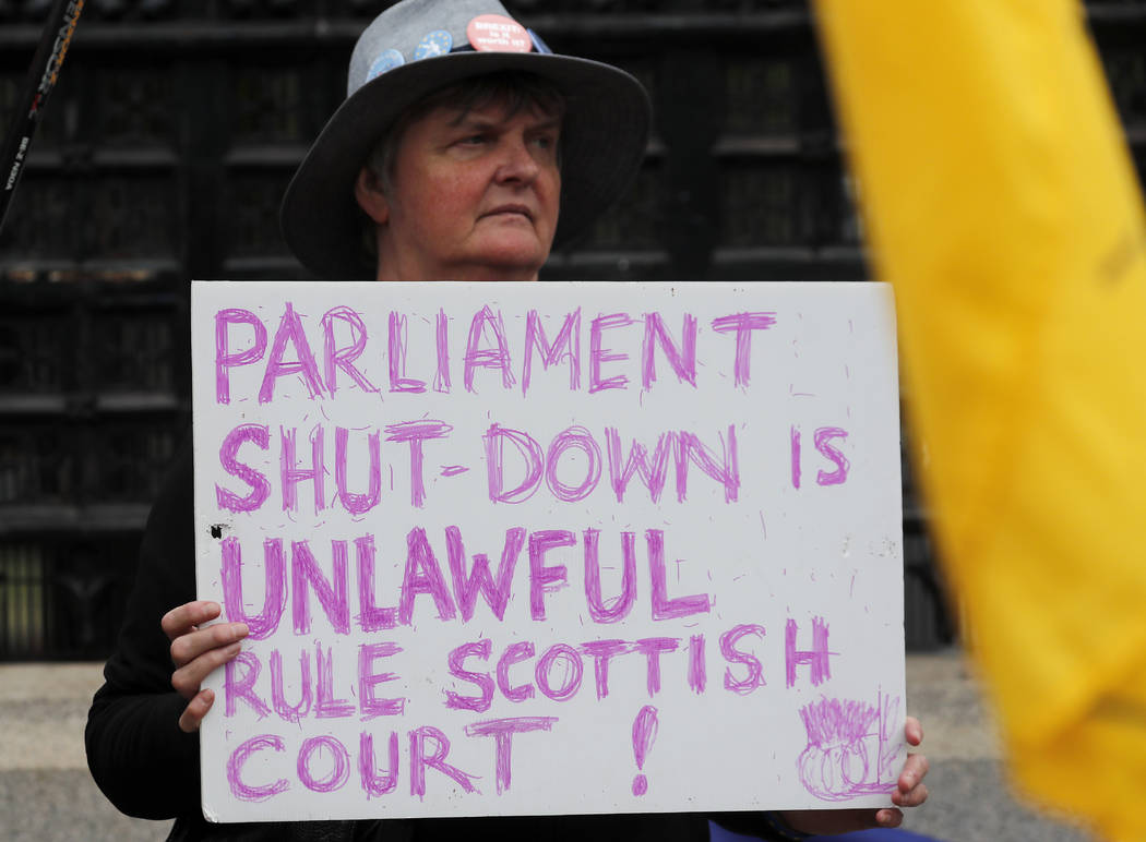A Pro EU protestor shows a poster in front of the Houses of Parliament entrance in London, Wedn ...