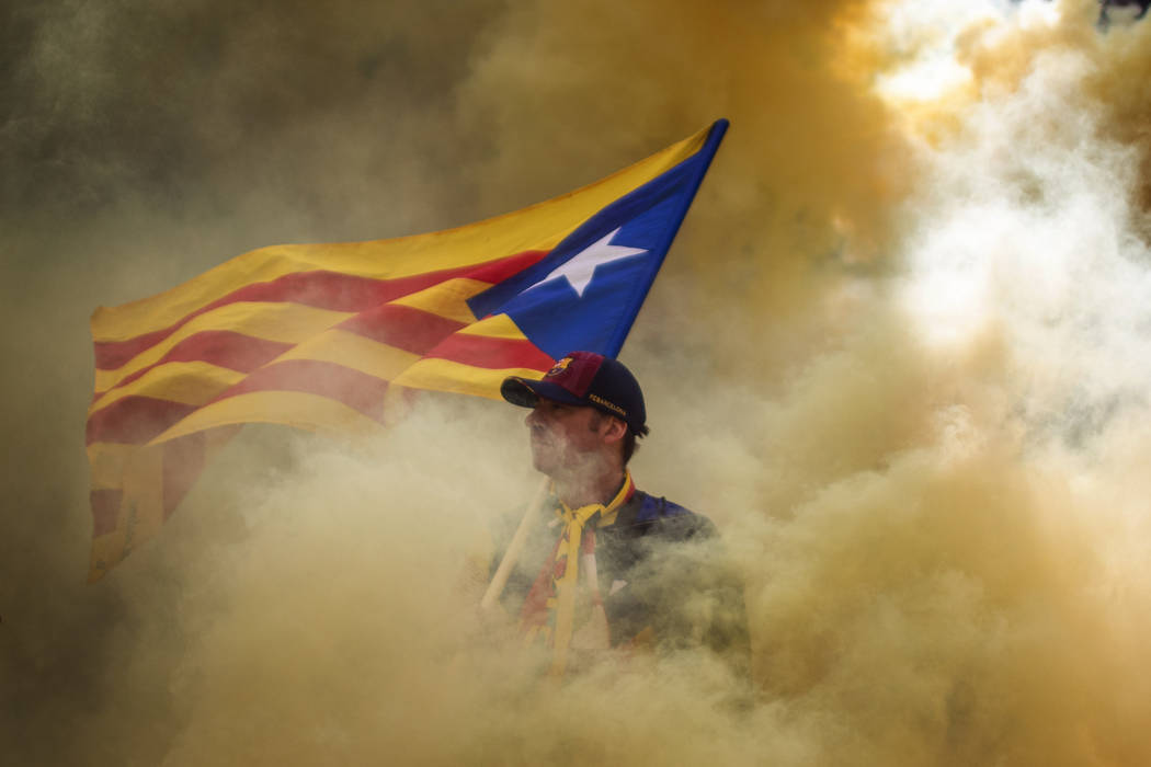 A man holding an independence flag is seen through the smoke thrown by demonstrators during the ...