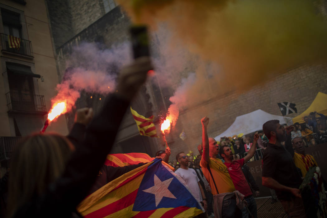 Protesters hold independence flags and flares during the Catalan National Day in Barcelona, Spa ...