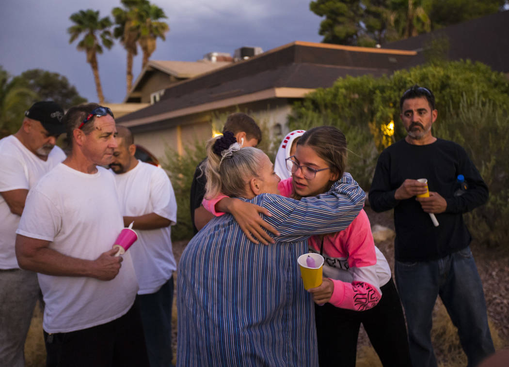 Kelsi Jackson, 15, center right, hugs her grandmother, Mary Ann Ratay, during a vigil in memory ...