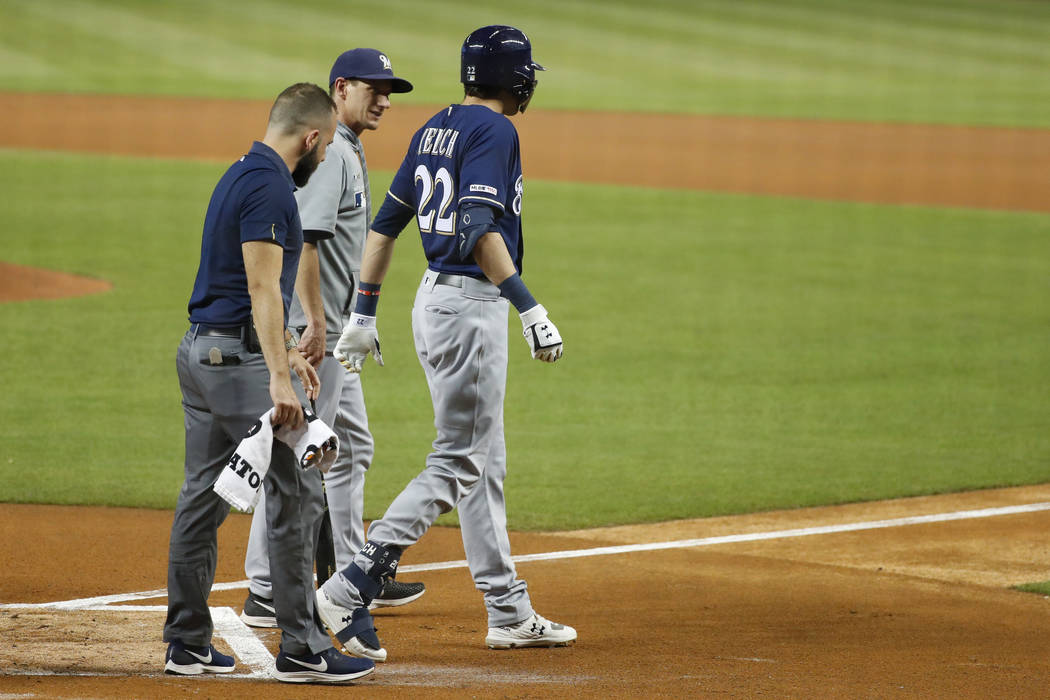 Milwaukee Brewers' Christian Yelich (22) walks off the field with a trainer and manager Craig C ...