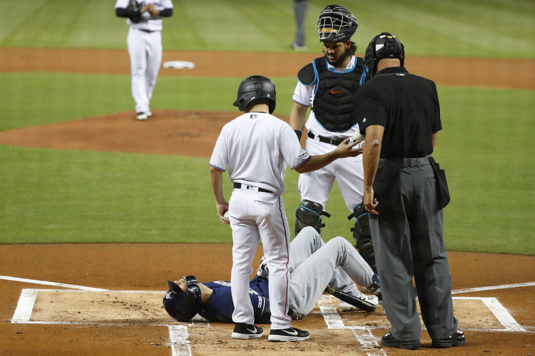 Milwaukee Brewers' Christian Yelich (22) lies on the ground after an injury during an at-bat, a ...