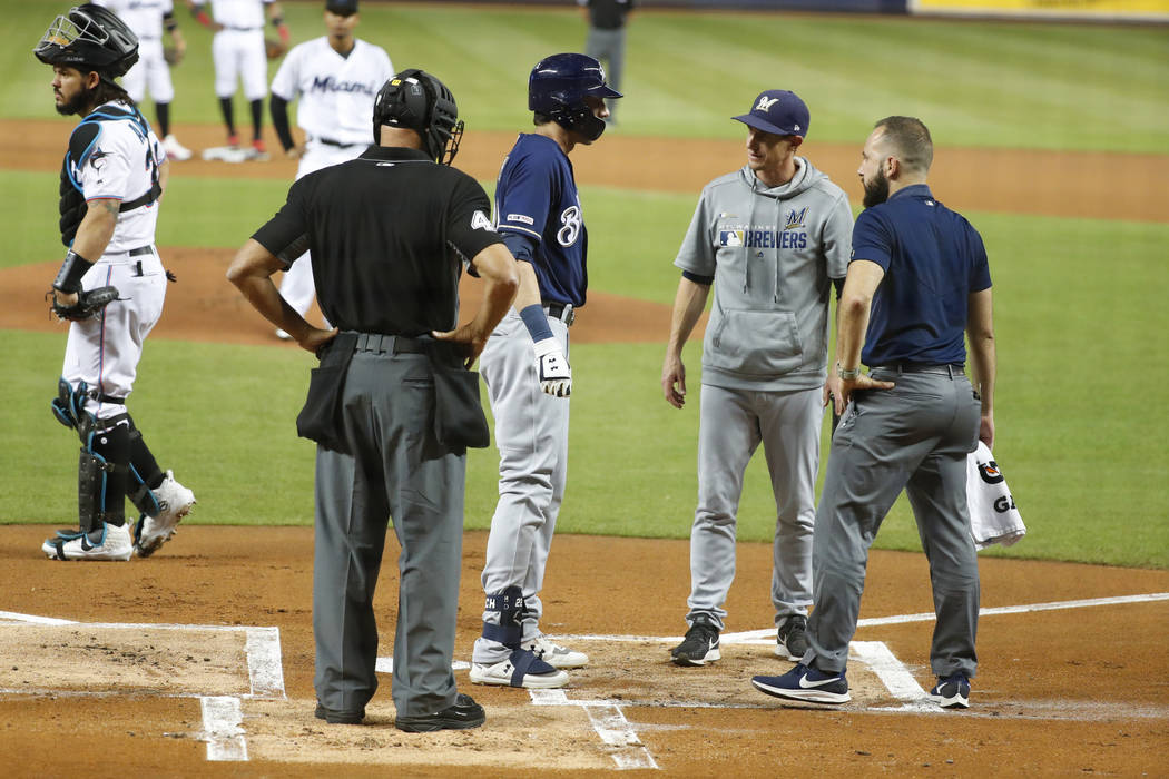 Milwaukee Brewers' Christian Yelich, second from left, is checked on by home plate umpire Kerwi ...
