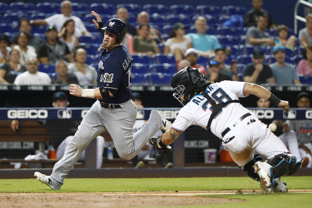 Milwaukee Brewers' Yasmani Grandal (10) heads for home plate to score on a sacrifice fly by Tyl ...