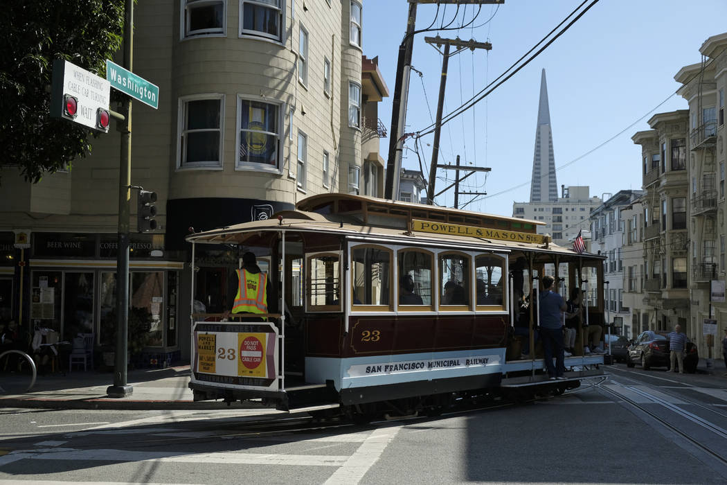 A cable car turns onto Washington Street with the Transamerica Pyramid in the background Wednes ...