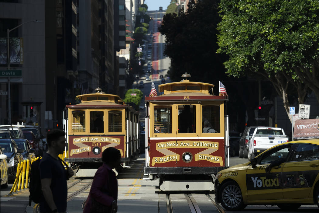 A cable car at right begins to make its way up California Street Wednesday, Sept. 11, 2019, in ...
