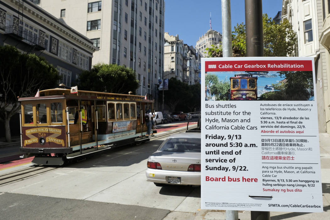 A cable car climbs California Street to Nob Hill past a sign announcing an upcoming rehabilitat ...