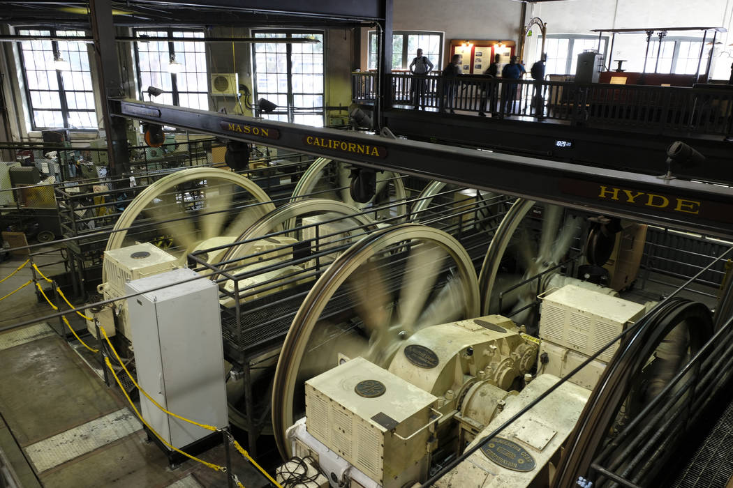 People stand above turning sheaves and gearboxes inside the cable car powerhouse Wednesday, Sep ...