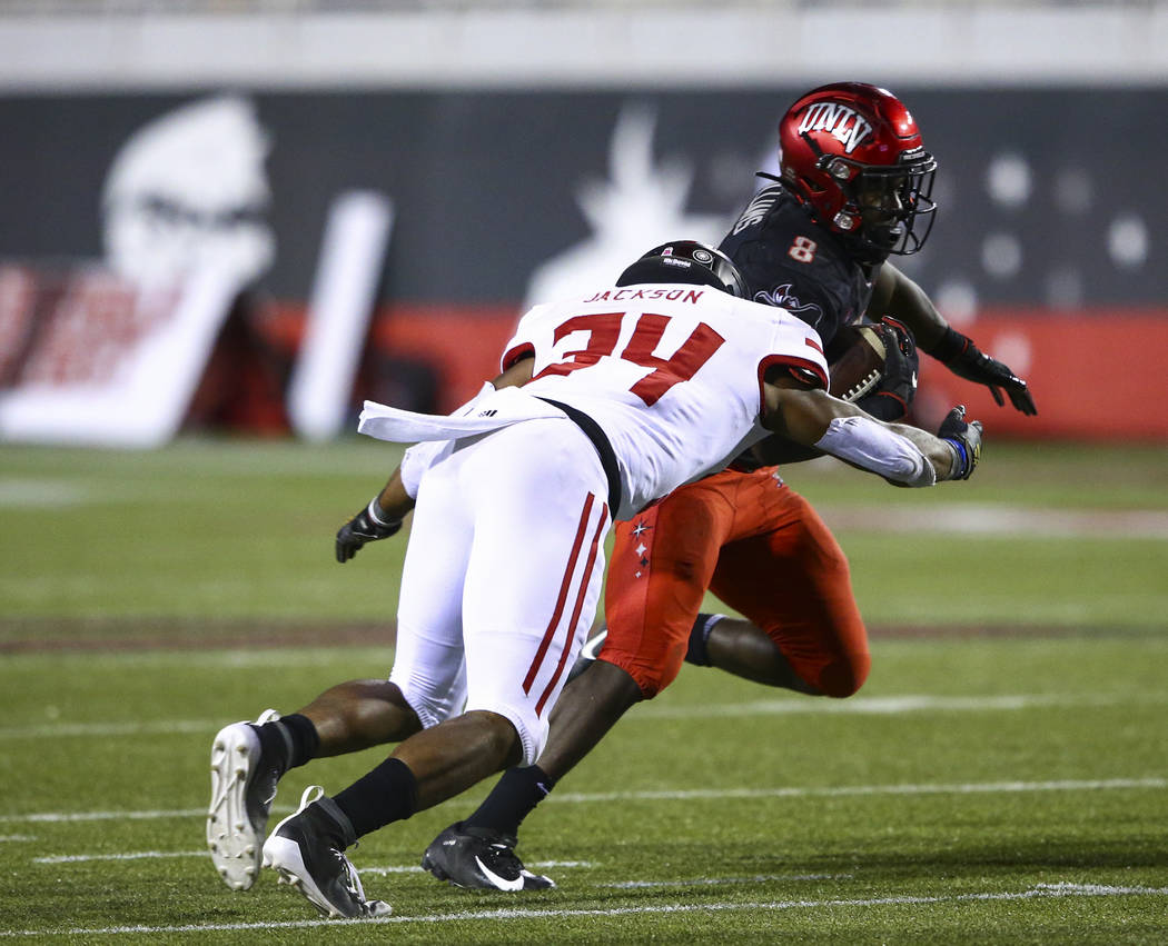 UNLV Rebels running back Charles Williams (8) tries to get past Arkansas State Red Wolves defen ...