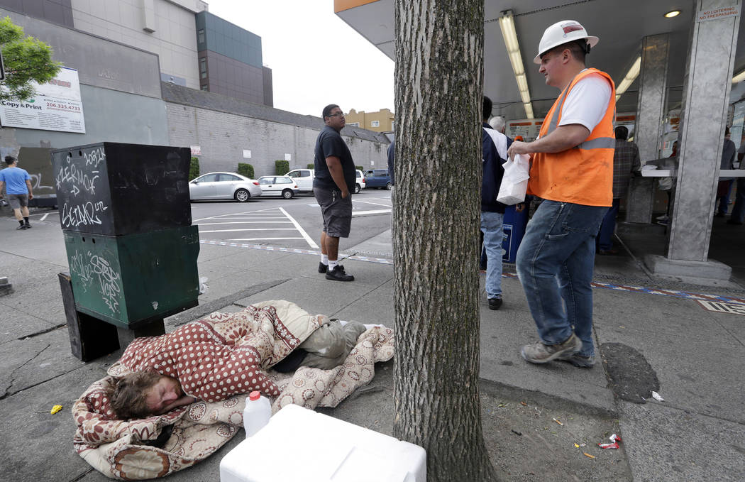 FILE - In this May 24, 2018 file photo, a man sleeps on the sidewalk as people behind line up t ...
