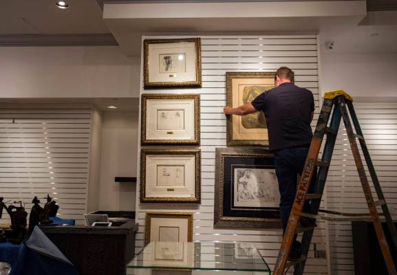 Chad Sampson, the Rick Harrison Collection art dDirector, places a drawing on the wall at the n ...