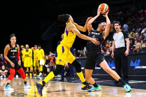Las Vegas Aces' Dearica Hamby, right, gets fouled by Los Angeles Sparks' Candace Parker during ...