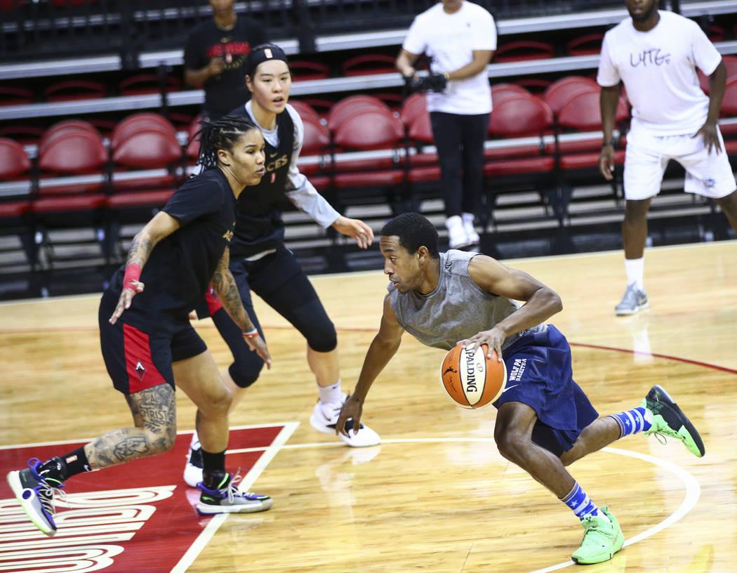 Adrian Dalton drives to the basket against Las Vegas Aces' Tamera Young, left, and Ji-Su Park d ...