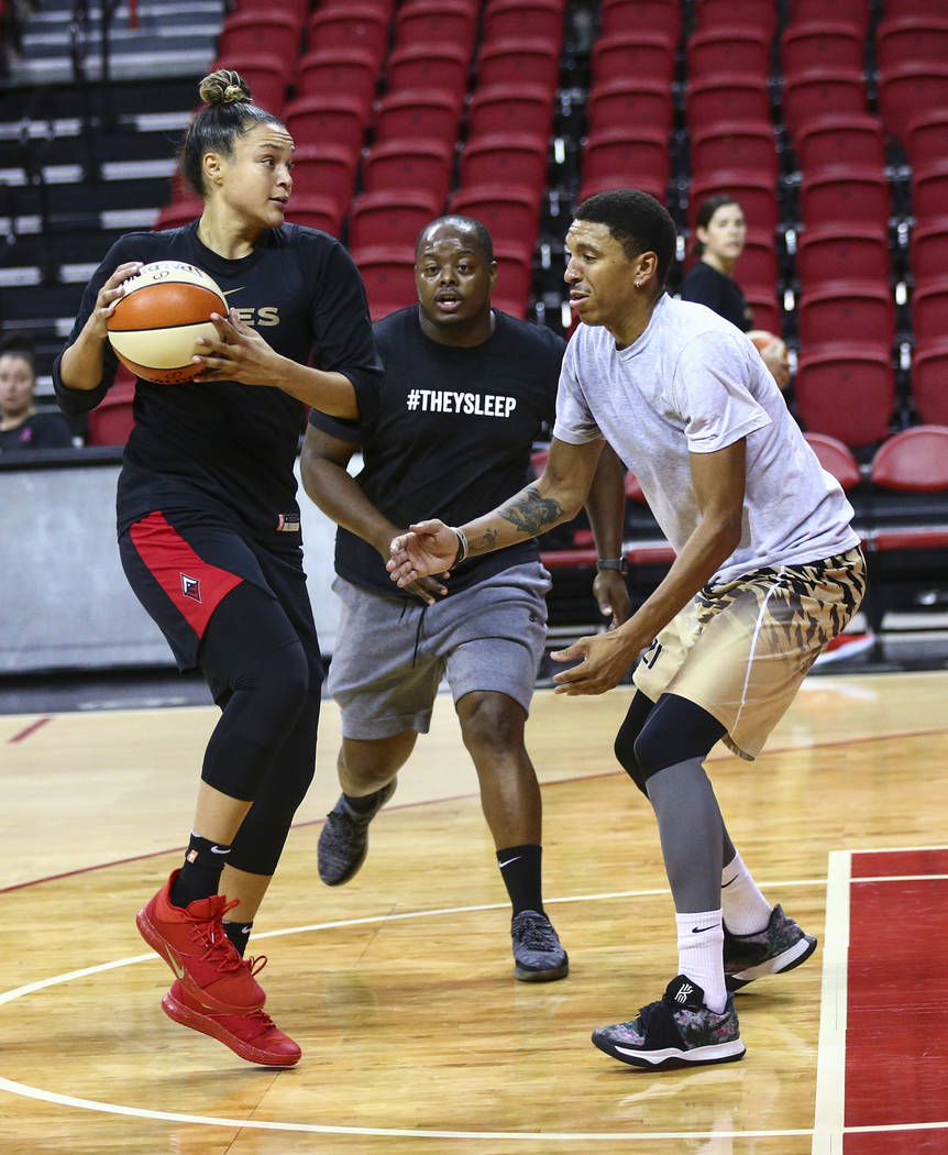 Las Vegas Aces' Kayla McBride, center, looks to pass the ball as Trevill Martin, from left, Dre ...