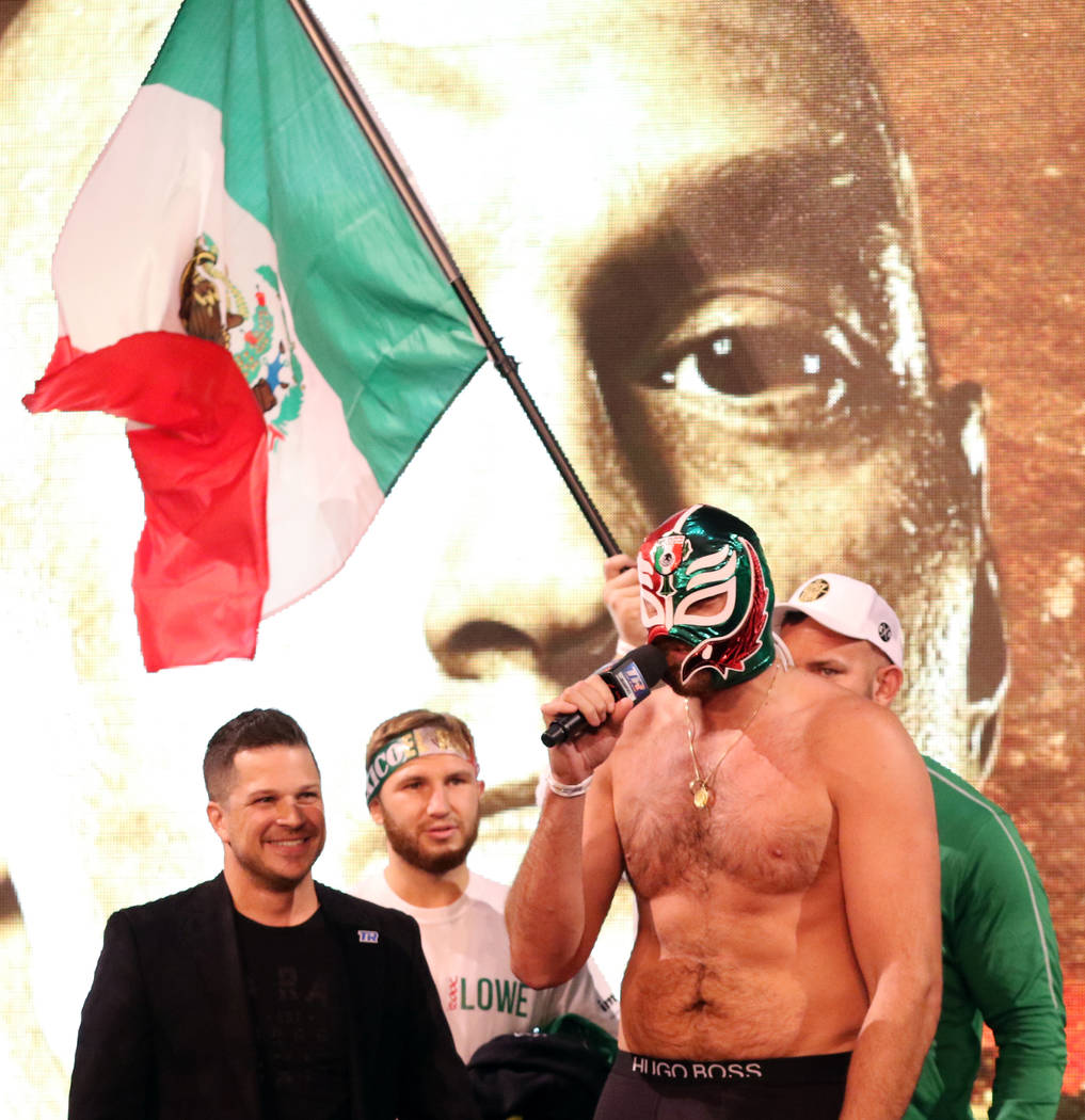 Boxer Tyson Fury wears a lucha libre mask as he speaks to the crowd at a weigh-in at the KA The ...