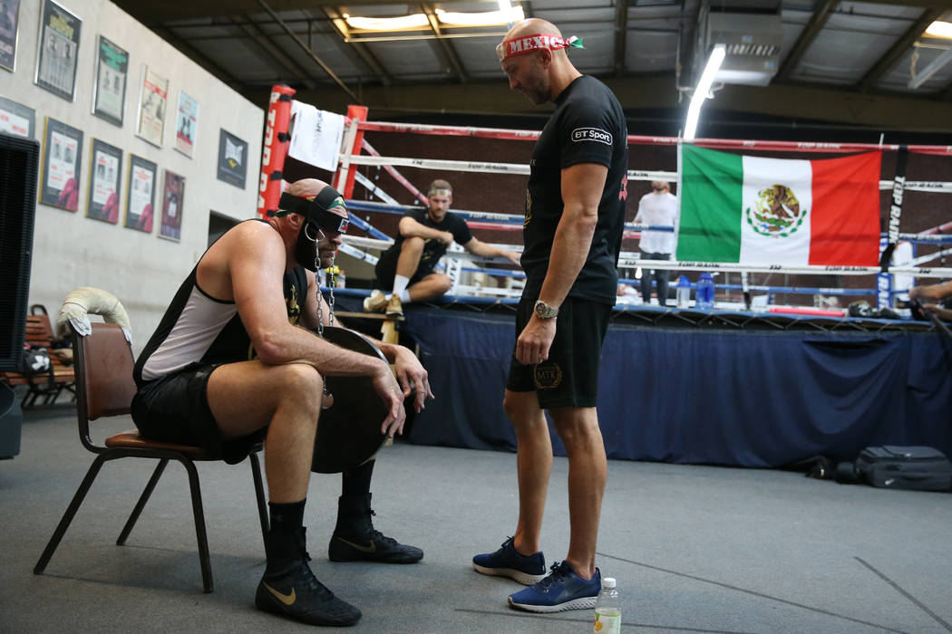 Tyson Fury, left, with his trainer Kristian Blacklock, works his neck by lifting weights with h ...