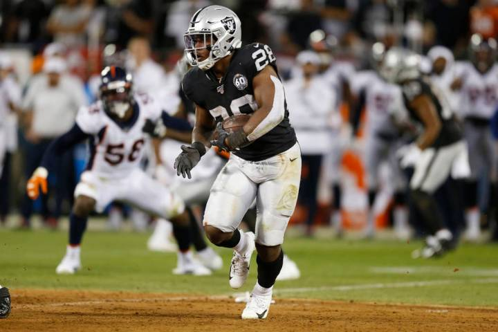 Oakland Raiders running back Josh Jacobs runs with the ball during the first half of an NFL foo ...