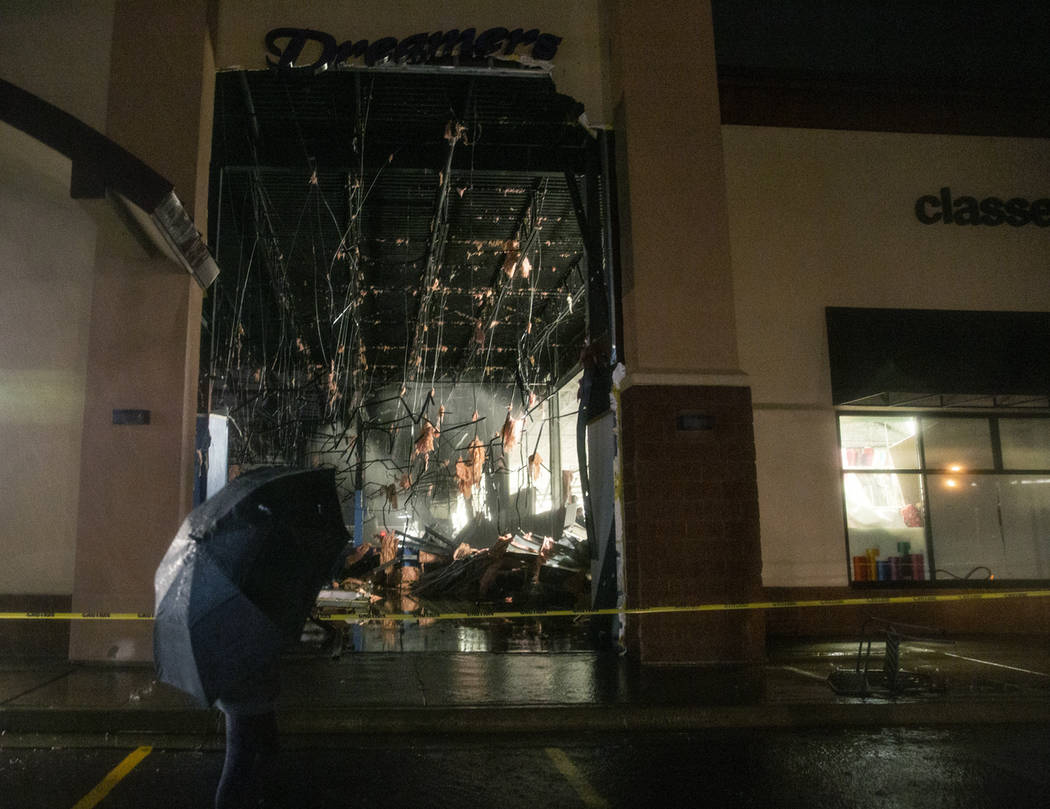 In this Tuesday, Sept. 10, 2019 photo, a passerby walks past a damaged store after severe weath ...