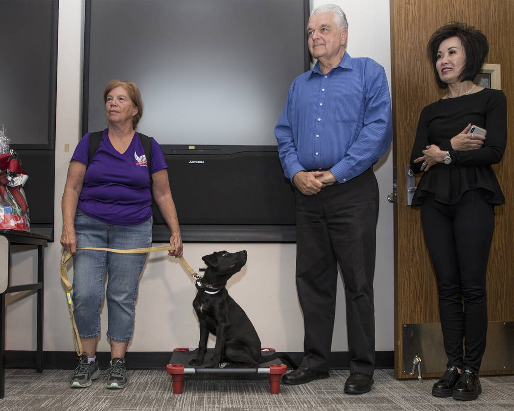 Linda Slates, left, office coordinator with Sit Means Sit Dog Training, holds the leash of ther ...