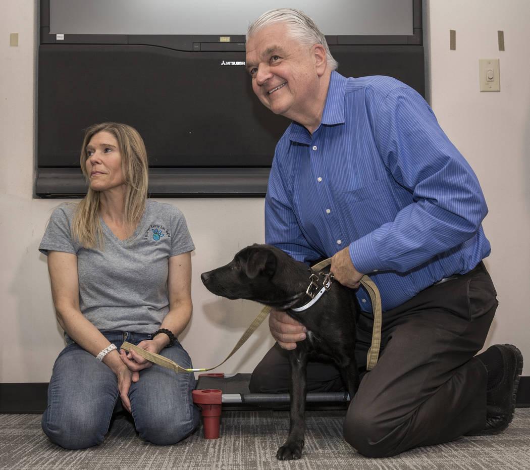 Gov. Steve Sisolak, right, with Danielle Roth, president of retriever rescue of Las Vegas, pets ...