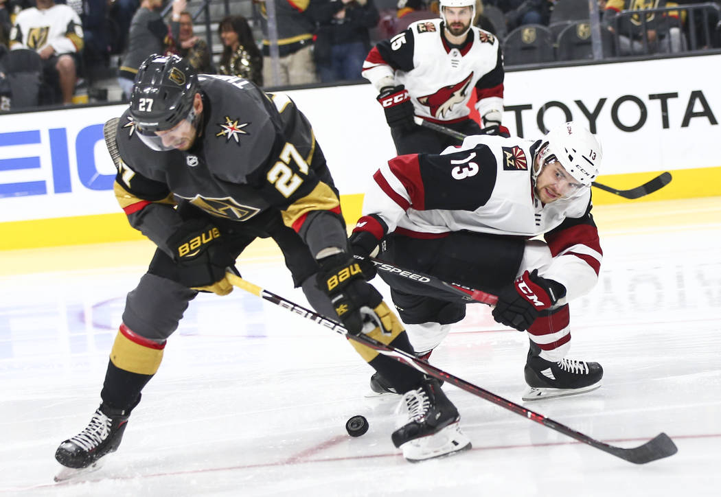 Golden Knights defenseman Shea Theodore (27) tries to get the puck from Arizona Coyotes center ...