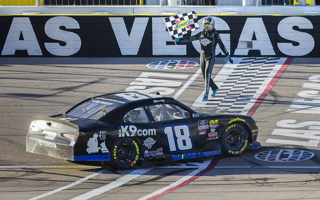 Kyle Busch (18) carries the checkered flag after winning the NASCAR Xfinity Series Boyd Gaming ...