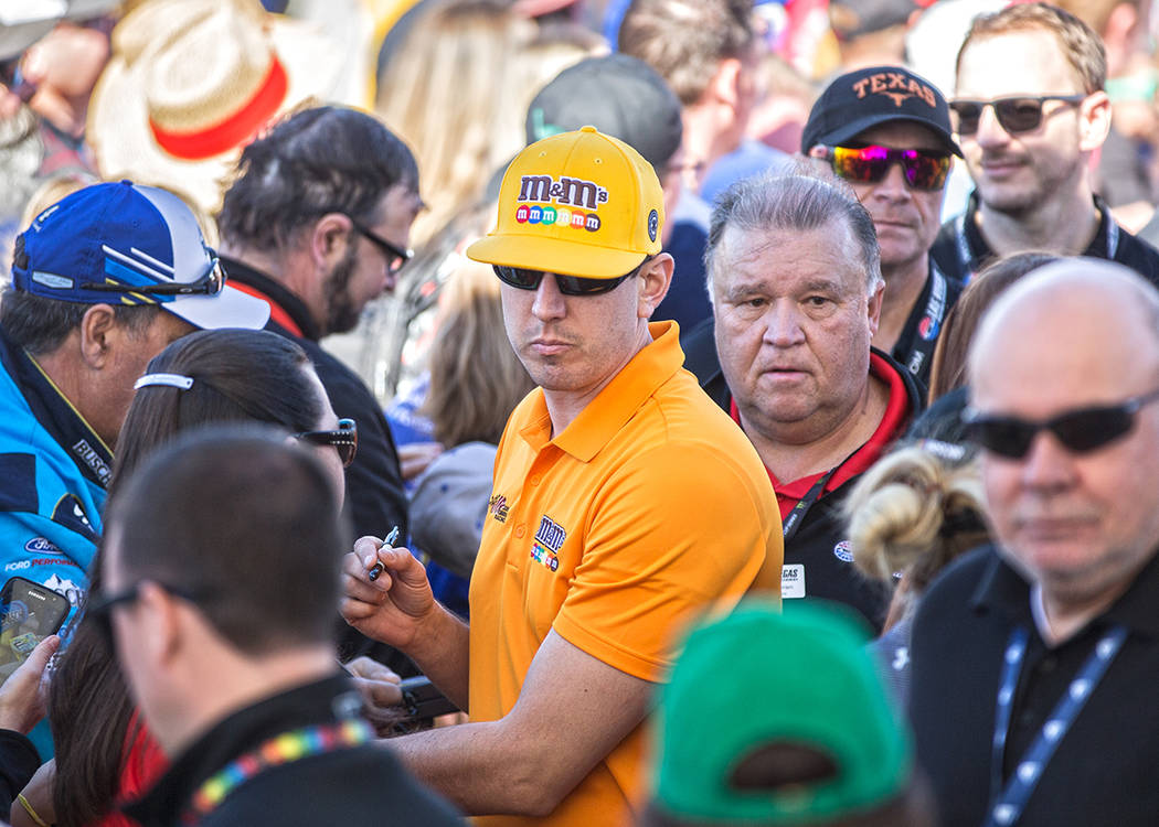 Kyle Busch, middle, signs autographs before the start of the Monster Energy NASCAR Cup Series P ...