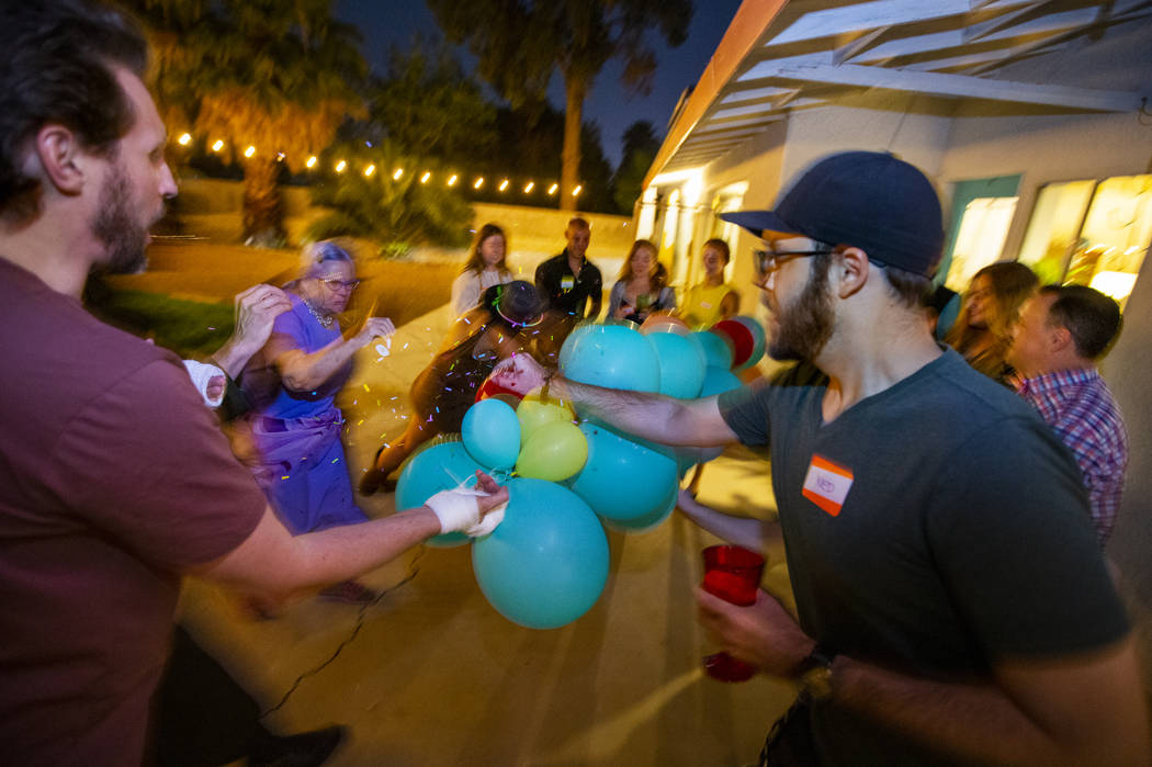 Guests pop balloons for a baby sex reveal during the secretive Oakey Family Supper Club event o ...
