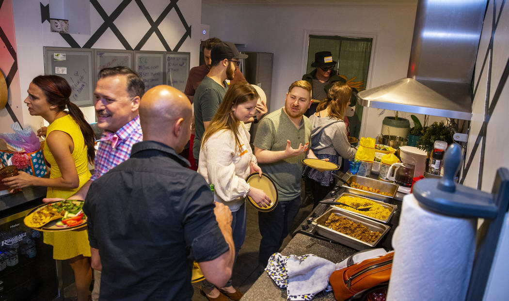 Guests gather in the kitchen for a buffet-style dinner during the Oakey Family Supper Club even ...