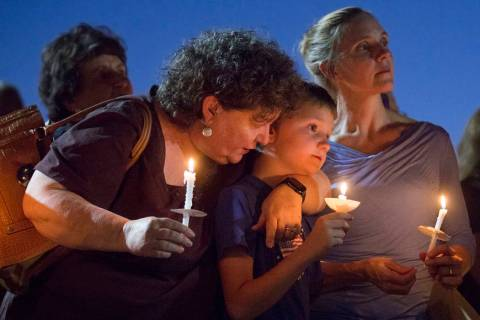 Paula Davis' brother Nathan Davis, center, holds a candle with his aunt Brenda Miraglia, left, ...
