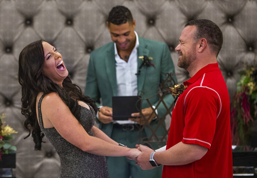 Laura and Justin Long hold hands and laugh as Vegas Golden Knights player Ryan Reaves, center, ...