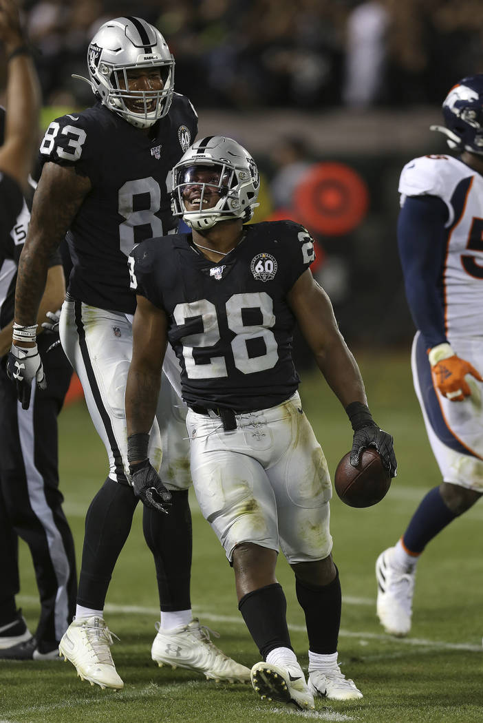 Oakland Raiders running back Josh Jacobs celebrates his first career touchdown with Darren Wall ...