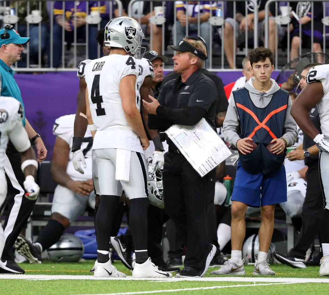 Oakland Raiders head coach Jon Gruden, right, has a conversation with quarterback Derek Carr (4 ...
