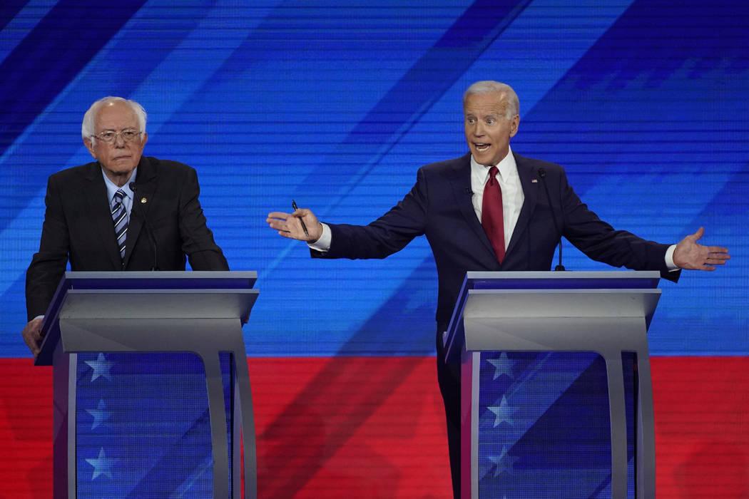 Sen. Bernie Sanders, I-Vt., left, listens as former Vice President Joe Biden, right, responds t ...