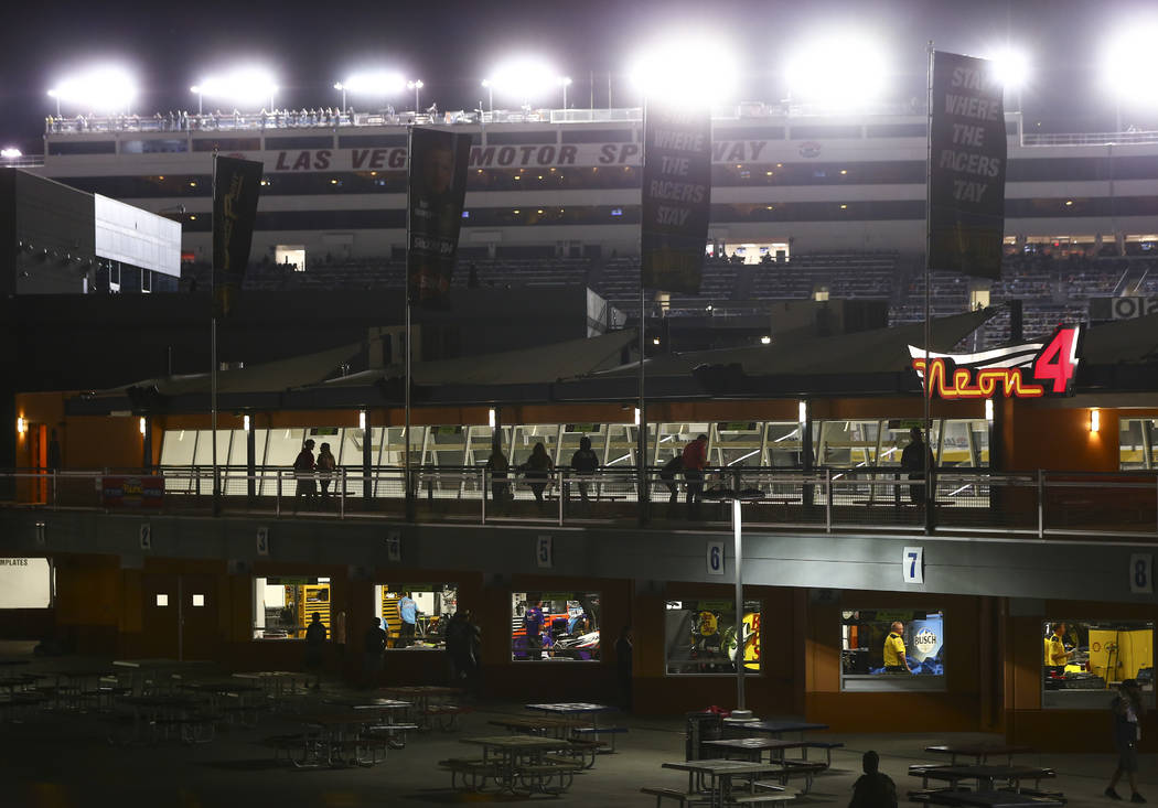 Attendees walk through the garage area as drivers compete during the NASCAR World of Westgate 2 ...