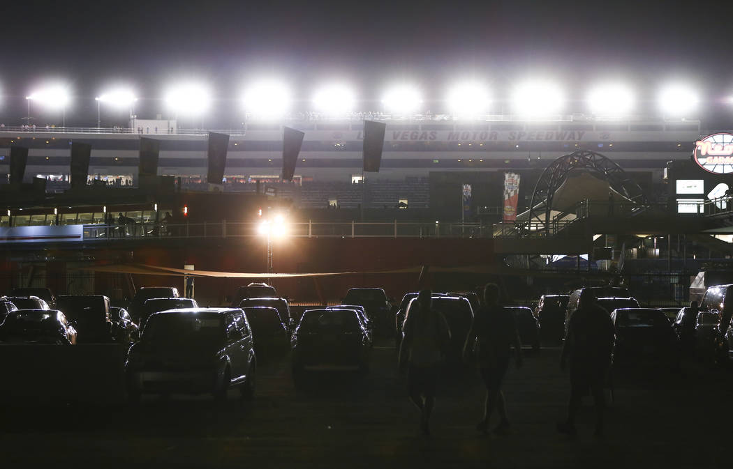 Attendees walk through a parking lot as drivers compete during the NASCAR World of Westgate 200 ...