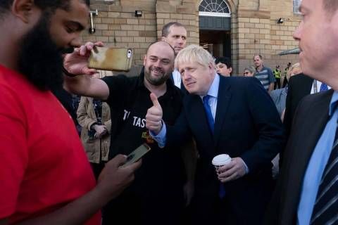 Britain's Prime Minister Boris Johnson poses for a selfie with a member of the publicduring a v ...