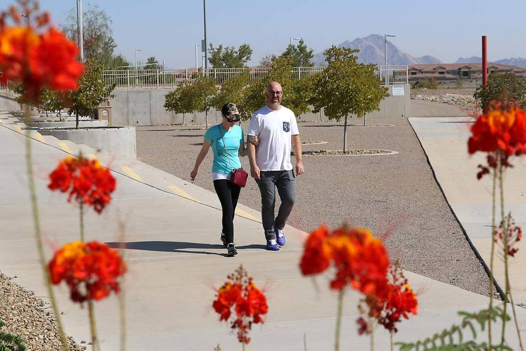 Adam Gnesia and his wife walk during a sunny morning at Cornerstone Park in Henderson. (Bizuaye ...
