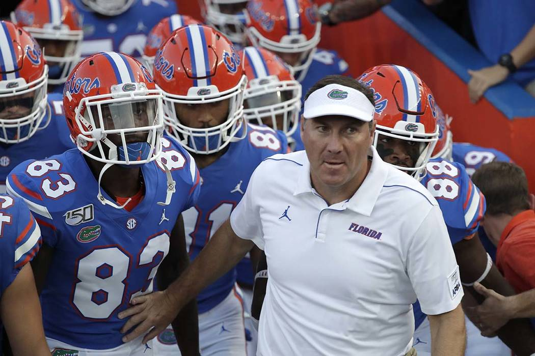 Florida head coach Dan Mullen takes the field with his players before an NCAA college football ...