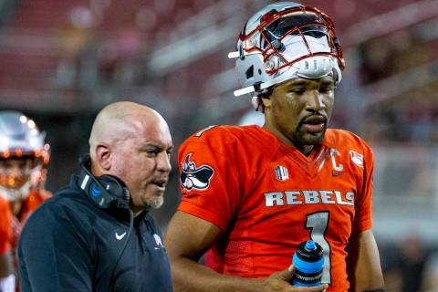UNLV Rebels head coach Tony Sanchez talks with quarterback Armani Rogers (1) after the first qu ...