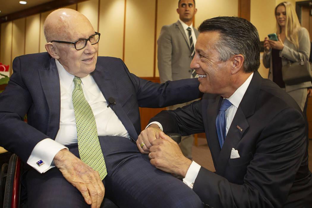 Former U.S. Sen. Harry Reid, left, pats the back of former Nevada Gov. Brian Sandoval, right, b ...