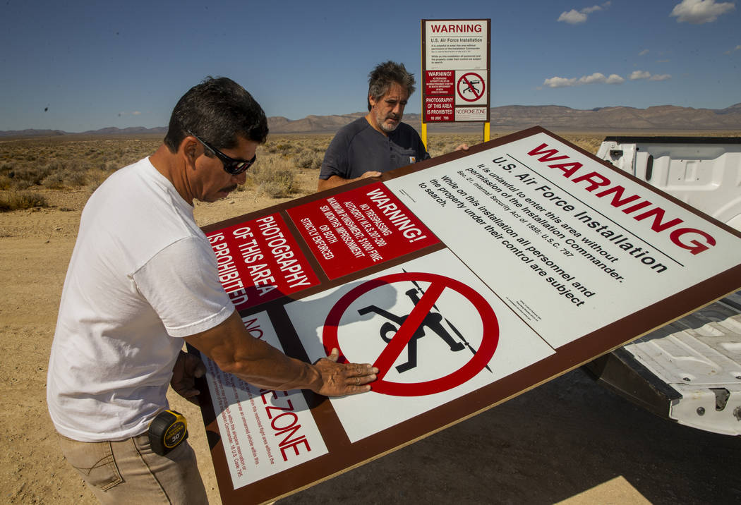 Dean Cruea, right, and Fred Hernandez with The Sign Shop of Las Vegas mount a mock Area 51 main ...