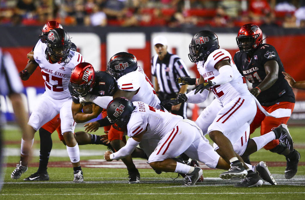 UNLV Rebels quarterback Armani Rogers (1) gets sacked by a phalanx of Arkansas State defenders, ...