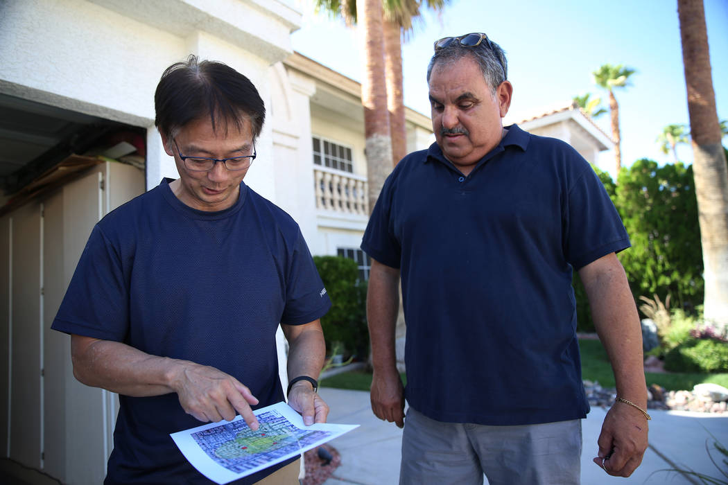 Wayne Niimi, left, in front of the home of his neighbor Victor Padron, shows on a map the three ...