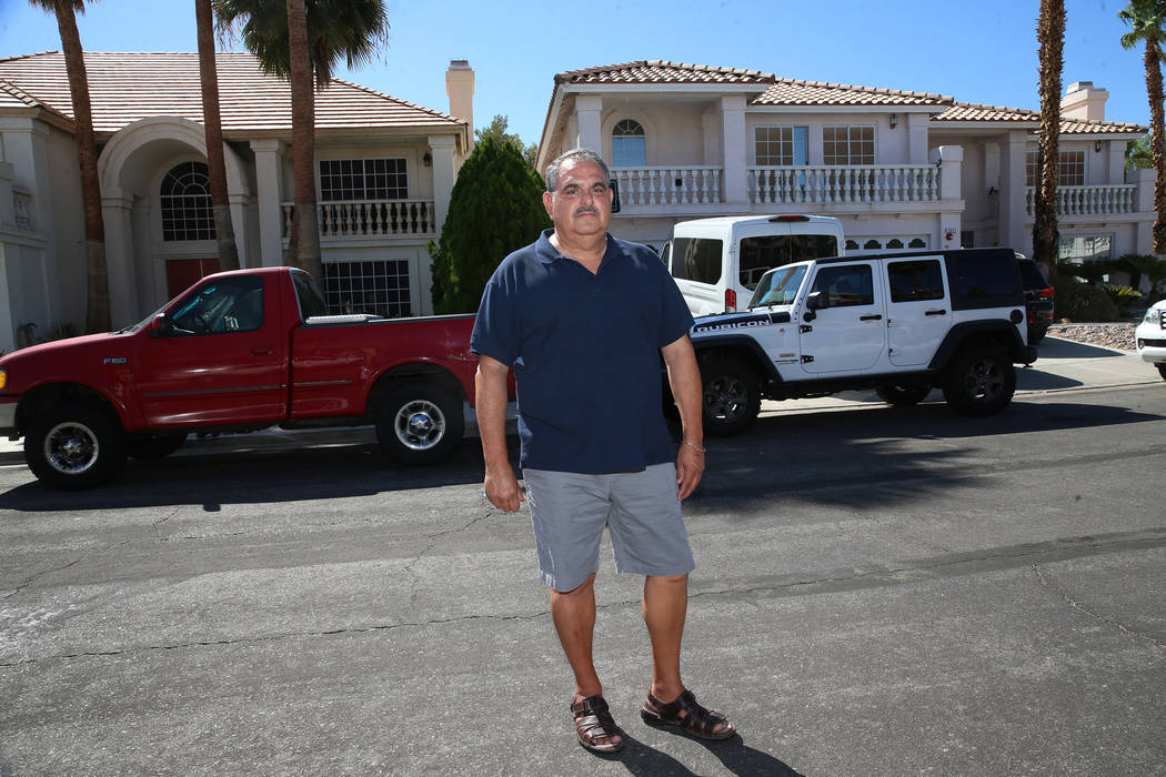 Victor Padron poses in front of his home, left, on Bahama Bay Court in Las Vegas, Thursday, Aug ...