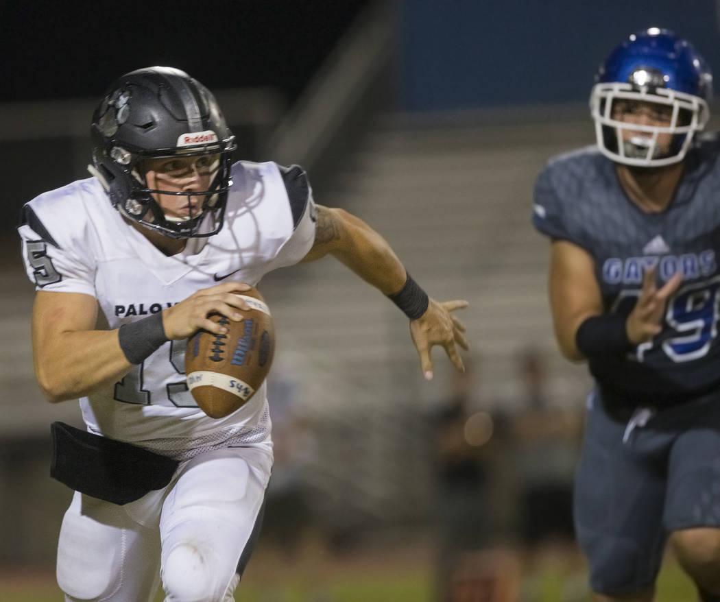 Palo Verde senior quarterback Paul Myro (15) scrambles past Green Valley senior defensive end Z ...