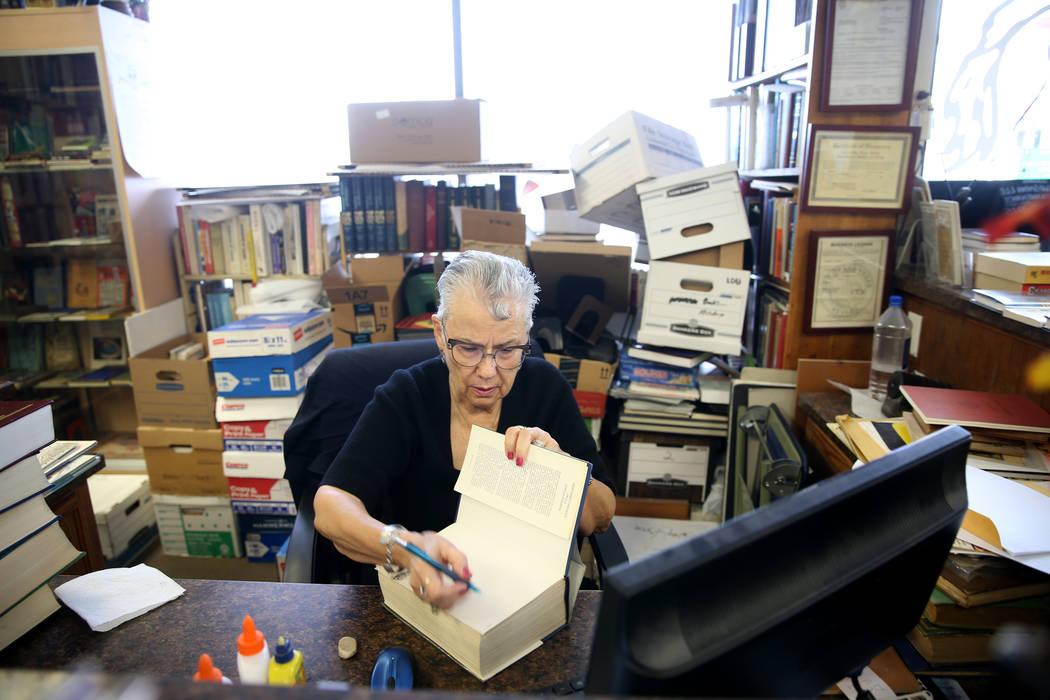 Myrna Donato, owner of Amber Unicorn Books at 2101 S. Decatur Blvd. in Las Vegas, prices a book ...