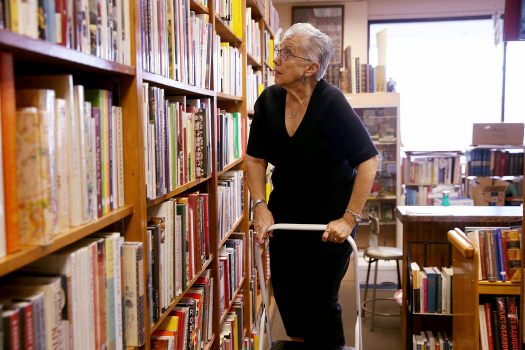 Myrna Donato, owner of Amber Unicorn Books at 2101 S. Decatur Blvd. in Las Vegas, prices a set ...