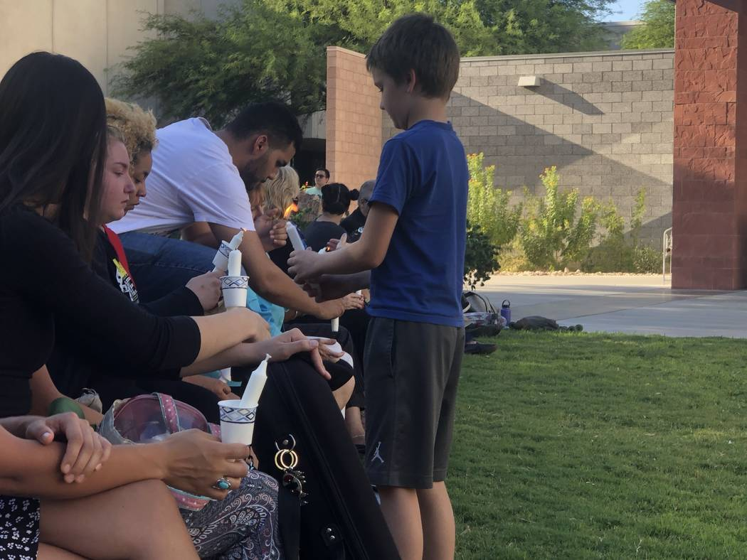 Nathan Davis helps light candles for those attending a vigil honoring his older sister at UNLV ...