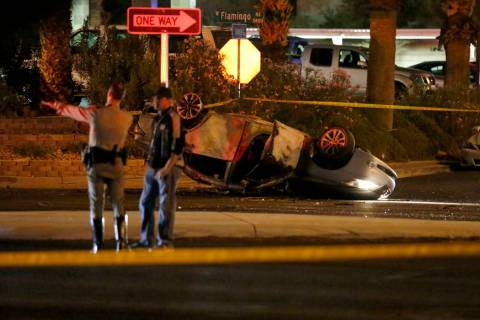 Las Vegas police officers investigate at the scene of a fatal crash at Flamingo Road and Dunevi ...